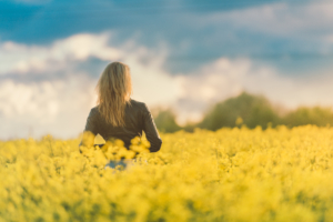 woman-standing-in-field-of-yellow-flowers