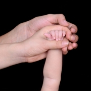 two adult hands holding a baby's hand