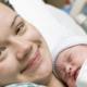 Smiling woman holding newborn baby